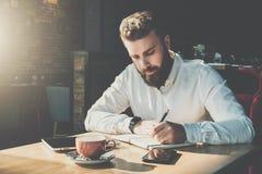 El hombre de negocios barbudo joven se sienta en café en la tabla y escribe en cuaderno En la tableta de la tabla, smartphone El  foto de archivo