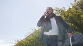 El hombre de negocios barbudo joven vestido en chaqueta está hablando en el teléfono mientras que él que se coloca cerca del edif almacen de video