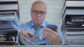 El hombre de negocios In Blurred Image hace pagos en línea con Smartphone y la tarjeta de banco imagen de archivo libre de regalías