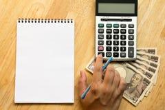 El hombre de negocios calcula con la calculadora, y tiene libro, japonés Foto de archivo libre de regalías
