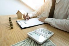 El hombre de negocios calcula negocio de la casa del precio de venta Ins casero del agente fotos de archivo