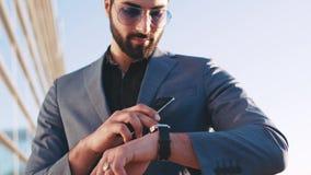 El hombre de negocios caliente en un traje, gafas de sol usando su teléfono, controles la época de su reloj elegante con el teléf almacen de video