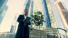El hombre de negocios camina con una tableta cerca de rascacielos, cierre para arriba