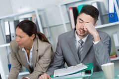 El hombre de negocios cansó solucionar problema en oficina con el compañero de trabajo fotografía de archivo