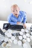 El hombre de negocios cansado bebe demasiado café en la oficina Imagenes de archivo