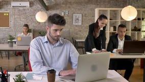 El hombre de negocios cansado joven está trabajando en la oficina, golpeando ligeramente en el ordenador portátil, discusión sobr almacen de video