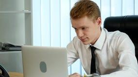 El hombre de negocios cansado joven que trabaja en su oficina delante del ordenador portátil parece agotado y usado almacen de metraje de vídeo