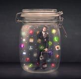 El hombre de negocios capturó en un tarro de cristal con estafa colorida de los iconos del app Foto de archivo libre de regalías