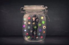El hombre de negocios capturó en un tarro de cristal con estafa colorida de los iconos del app Imágenes de archivo libres de regalías