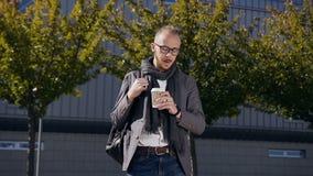 El hombre de negocios caucásico joven está bebiendo el café en la ciudad de centro moderna outdoors El caminar barbudo joven del  almacen de metraje de vídeo