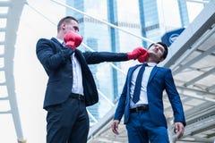 El hombre de negocios caucásico lleva guantes de boxeo rojos perfora para hacer frente de hombre de negocios asiático Concepto de imágenes de archivo libres de regalías