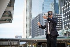 El hombre de negocios cauc?sico que lleva las auriculares VR de la realidad virtual y se imagina para conducir un coche fotografía de archivo