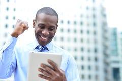 El hombre de negocios celebra su éxito con la tableta Foto de archivo libre de regalías