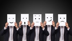El hombre de negocios cinco que sostiene una tarjeta con sensaciones de la emoción de las expresiones faciales del dibujo diversa foto de archivo