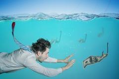 El hombre de negocios codicioso está nadando en agua y dinero de cogida en cebo Concepto del fraude imagen de archivo