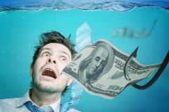 El hombre de negocios codicioso está nadando en agua y dinero de cogida en cebo Concepto del fraude fotos de archivo libres de regalías