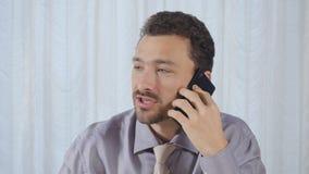 El hombre de negocios come el baguette y habla en el teléfono metrajes