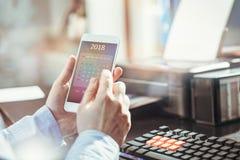 El hombre de negocios comprueba el calendario en su smartphone Imágenes de archivo libres de regalías