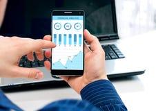 El hombre de negocios comprueba el análisis financiero en smartphone Foto de archivo libre de regalías
