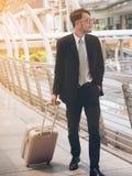 El hombre de negocios con el bolso del viaje está en viaje de negocios fotografía de archivo
