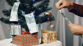 El hombre de negocios con el dinero adorna el árbol de navidad almacen de metraje de vídeo