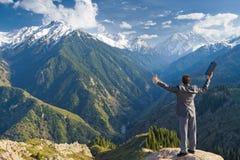 El hombre de negocios con el ordenador portátil en la cima de la montaña está por favor Imagen de archivo