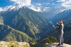 El hombre de negocios con el ordenador portátil en la cima de la montaña está por favor Foto de archivo libre de regalías