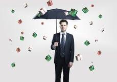 El hombre de negocios con el paraguas bajo los rectángulos de regalo llueve Imagen de archivo libre de regalías