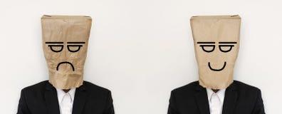 El hombre de negocios con la bolsa de papel arrugada con cólera agujereó la cara, y alisa la bolsa de papel con la cara sonriente Foto de archivo