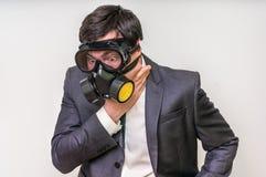 El hombre de negocios con la careta antigás no puede respirar el mún aire fotografía de archivo libre de regalías