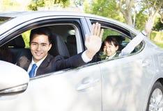 El hombre de negocios con la hija que conduce el coche va a trabajar y a enseñar fotos de archivo libres de regalías