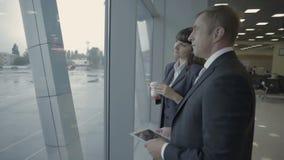 El hombre de negocios con la tableta habla con el empleado del aeropuerto cerca de la ventana en aeropuerto almacen de metraje de vídeo