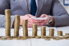 El hombre de negocios con las monedas de oro en concepto del crecimiento del negocio fotografía de archivo libre de regalías