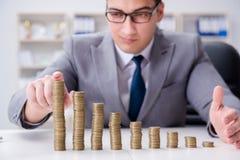 El hombre de negocios con las monedas de oro en concepto del crecimiento del negocio Foto de archivo libre de regalías