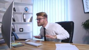 El hombre de negocios con los brazos aumentó la celebración de éxito en oficina almacen de video