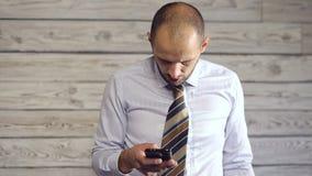 El hombre de negocios con smartphone disfruta de buenas noticias almacen de video