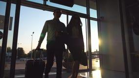 El hombre de negocios con su colega femenino que camina entra a través a la maleta del terminal y del rollo en las ruedas Hombre  metrajes