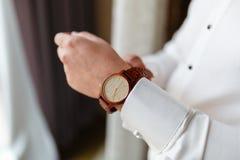 El hombre de negocios con un reloj costoso abotona vínculo de puño en la camisa blanca de lujo de las mangas francesas de los puñ fotos de archivo