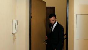 El hombre de negocios con una barba y un traje y un lazo entra en la puerta de la oficina 4K v?deo 4K almacen de video