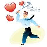 El hombre de negocios con una red coge el corazón rojo que vuela Imagen de archivo libre de regalías