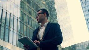 El hombre de negocios con una tableta mira los rascacielos, cierre para arriba