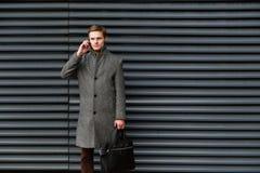El hombre de negocios confiado joven en una capa y una cartera grises en su mano está hablando en el teléfono móvil contra la par fotos de archivo