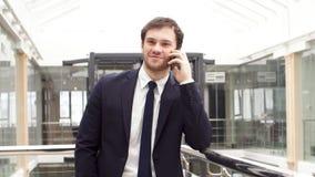 El hombre de negocios confiado joven es negociación corporativa en el smartphone en pasillo de la oficina moderna almacen de video