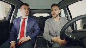 El hombre de negocios confiado joven está discutiendo el nuevo coche con el vendedor profesional que se sienta en asientos delant almacen de metraje de vídeo