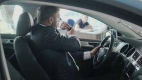 El hombre de negocios consigue llaves del ` un s del coche de vendedor en el giroscopio en concesión de coche metrajes