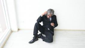 El hombre de negocios consiguió malas noticias vía el teléfono y muestra la sensación muy trastornada en el fondo blanco de l