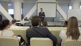El hombre de negocios contesta a las cuestiones de sus colegas en la presentación en la oficina metrajes