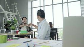 El hombre de negocios creativo asiático elegante hermoso acertado y sus brazos de los colegas aumentaron la celebración de la sen metrajes