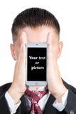 El hombre de negocios cubrió su cara con un teléfono Fotografía de archivo libre de regalías