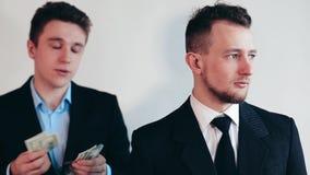 El hombre de negocios cuenta el dinero detrás de la parte posterior almacen de metraje de vídeo
